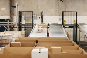 Packages being transported through warehouse on conveyor belts.